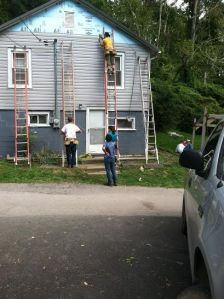 One of the groups works on siding a house.